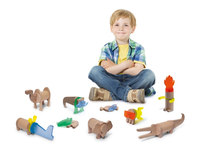 Boy sitting next to construction blocks and smiling
