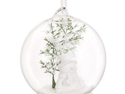 Bola de Navidad de cristal y follaje verde